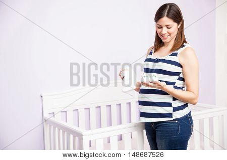 Pregnant Woman Looking At Baby Clothes