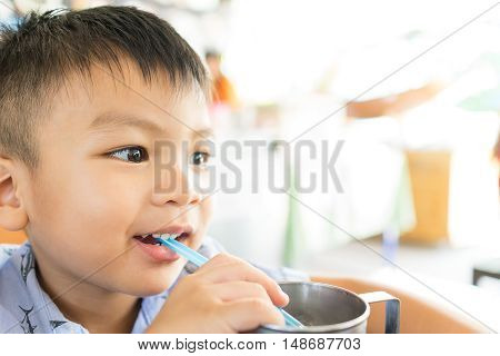 Asian boy is drinking cold water through straw