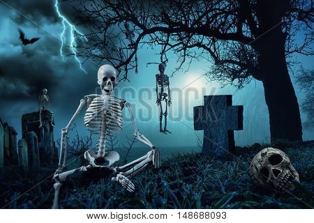 Nighttime Halloween scene with skeletons at a cemetery and the silhouette of a dead tree in the blue moonlight