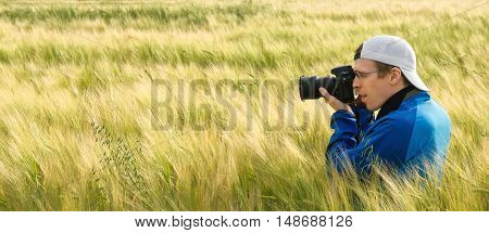 Wide format image of a photographer sitting amidst beautiful barley plants on a field and aiming the camera