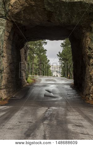 A narrow road tunnel with a view of Mount Rushmore.