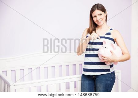 Portrait of a beautiful young pregnant brunette emphasizing the importance of saving money during pregnancy
