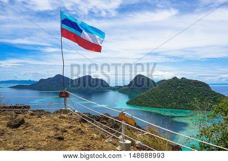 Semporna,Sabah-Sep 10,2016:Sabah flag at the top of the Bohey Dulang tropical island,Semporna,Sabah.Bohey Dulang Island is one of the most popular islands in Tun Sakaran Marine Park.