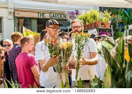London United Kingdom - September 11 2016: Columbia Road Flower Sunday market. Street traders are selling their stock people choosing flowers