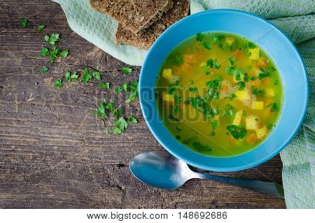 Zuppa Imperiale - Italian soup with eggs and Parmesan cheese dish of Emilia Romagna. Imperial soup on wooden table. Omelet in chicken broth with parsley in a bowl. Italian cuisine concept. Top view.