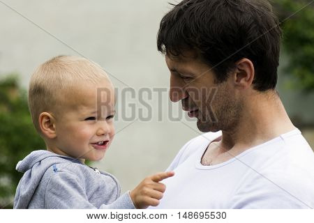 Boy and his uncle are outdoors. The little boy shows to something.