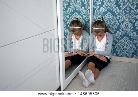 Little aggrieved girl sitting in the corner of her room near the mirror head down