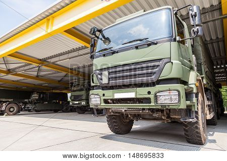 a military truck stands under military roof
