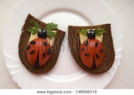 Ladybug from tomato and olives. Ridiculous food for good mood. The ladybug is located on bread.