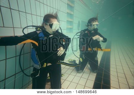 Two women are standing on knees with equipment for diving in the pool.