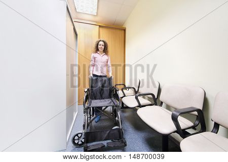 Wheel chair stands in lobby of hospital ready to transport patient is woman behind chair