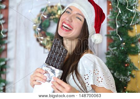 lovely woman with elegant style in Santa cap standing near door of house sham and holding large bar of chocolate, smiling