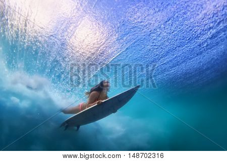 Sportive girl in bikini in action. Surfer with surf board dive underwater under breaking ocean wave. Healthy lifestyle. Water sport swim and extreme surfing in adventure camp on summer beach vacation