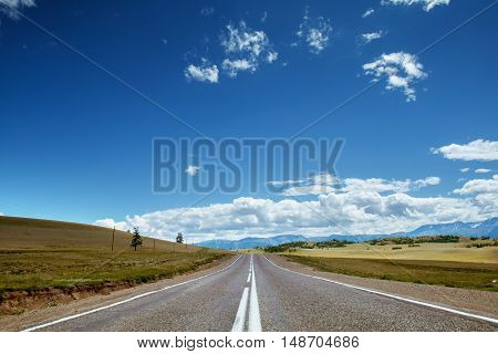Straight road goes to horizon on background of sky and mountains. Altay mountains, Siberia, Russia.