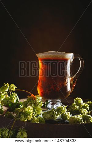 Antique glass tankard filled with ale on a rustic barrel with hops