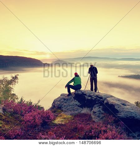 Hiker and photo enthusiast stay with tripod on cliff and takes photos. Dreamy fogy landscape blue misty sunrise in a beautiful valley below