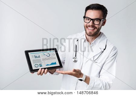 The best results ever. Young handsome doctor smiling and showing diagrams on tablet while standing against white background.