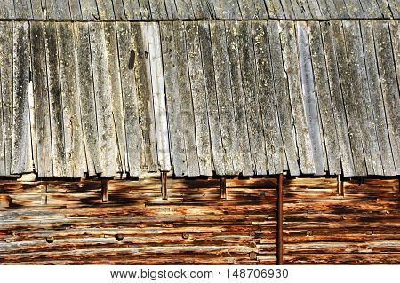 Closeup of log barn shows notched and fitted logs. Roof line is layered weatherd boards.