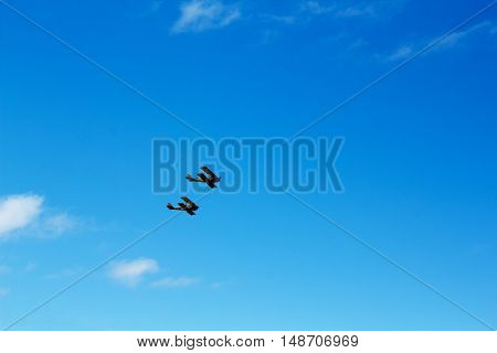 Pair of biplanes against a clear blue sky