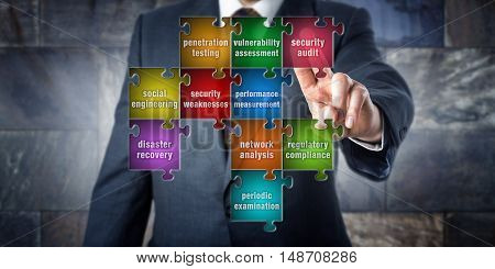 IT manager is doing a virtual puzzle made of pieces labeled with security audit terminology. Information systems concept for computer security audit vulnerability assessment and penetration testing.