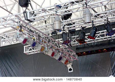 Stage lights attached by metal framework to top of theater