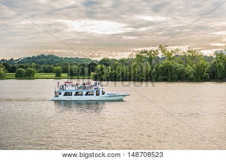 Washington DC, USA - August 4, 2016: Yacht boat on Potomac river during sunset with people