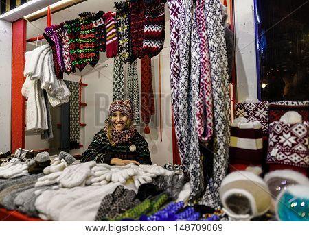 Smiling Woman Sells Warm Clothes At Riga Christmas Market