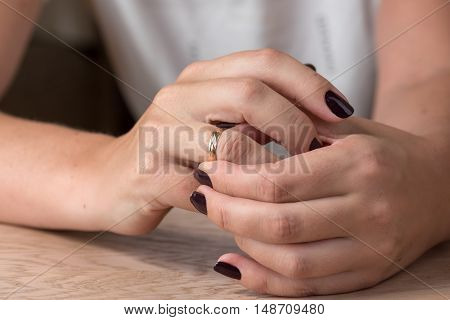 Divorce, separation: hands of woman removing wedding or engagement ring poster
