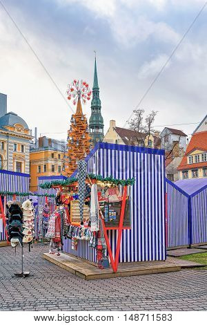 Riga Latvia - December 26 2015: Some stalls and the Christmas tree at the Livu square in old Riga Latvia. The Christmas market is the traditional part of celebrations. Selective focus