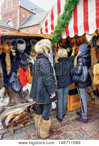 Riga Latvia - December 25 2015: Random people pictured while choosing fur clothes at one of the stalls at the Christmas Market in the old town of Riga Latvia.