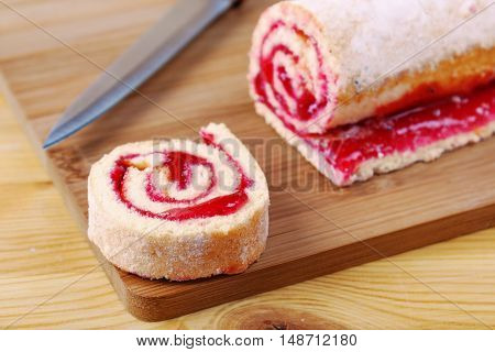 Sweet Roll With Jam And A Knife On A Cutting Board.