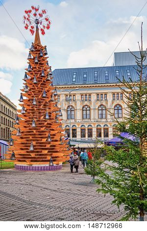 People Walking Around The Wooden Christmas Tree In Riga