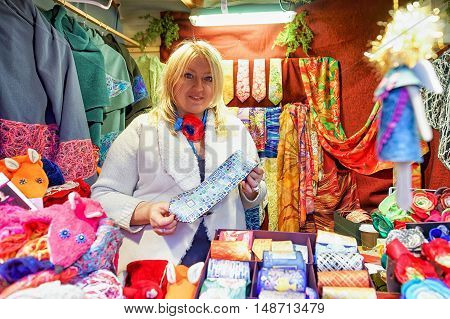 Woman Offering Festive Ties At Riga Christmas Market