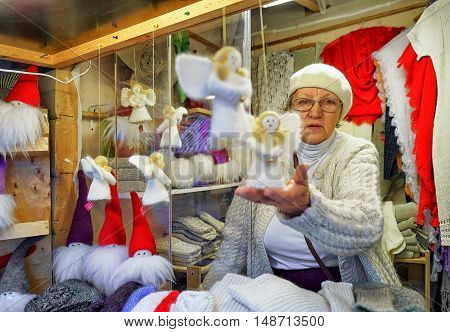 Woman Selling Handmade Angel Statues At Riga Christmas Market