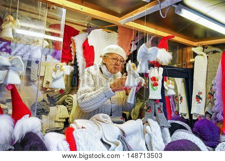Woman Selling Handmade Angel Statues At The Riga Christmas Market