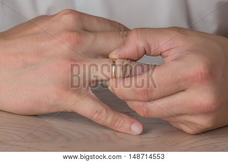 Divorce, separation: hands of man removing wedding or engagement ring