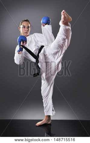 Beautiful young black belt female karate doing kick on the gray background
