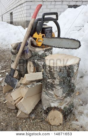 Birch firewood and a chainsaw with ax poster