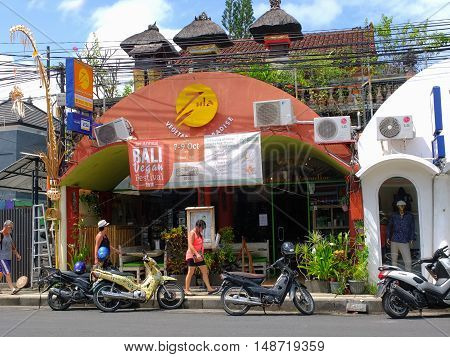 BALI, INDONESIA - SEPTEMBER 17, 2016: Tourists walking past a vegan restaurant, Bali, Indonesia.