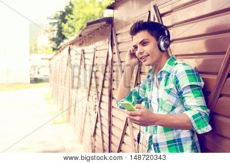 Modern young millennial man with headphones and smart phone outdoors. Cool teenage guy smiling, listening to music. Natural light, retouched, color filter applied.