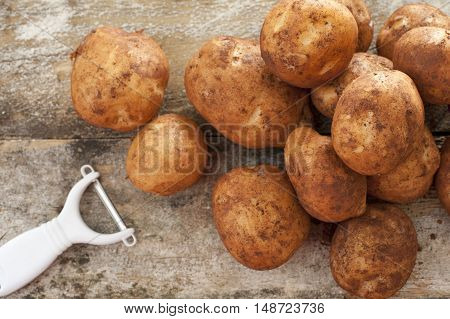 Pile of round baking potatoes beside peeler against a rustic background as seen from an overhead view