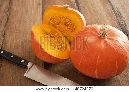 Small round oddly shaped pumpkin cut in middle beside bigger one and a large sharp knife