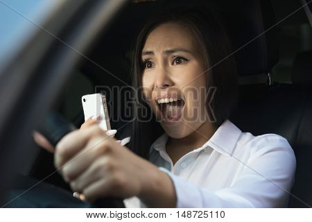 Young pretty asian scared woman driving in the car
