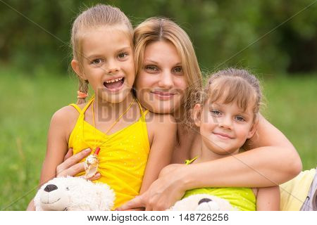 Young Mother Hugging Her Two Daughters, Five And Seven Years