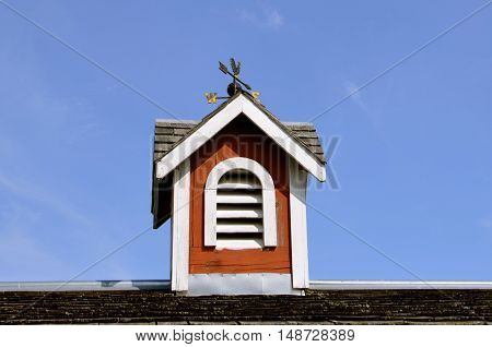 A wooden red cupola on a barn roof also has a wind vane