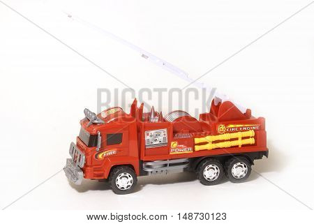 An isolated red fire truck toy over a white background.
