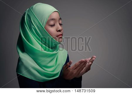 Young muslim girl praying Isolated on grey background