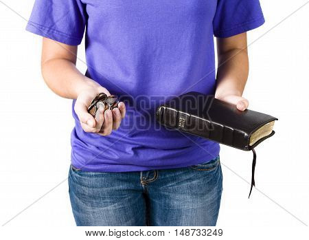 Young teenager holding money and a Bible as if she is making the choice between God and wealth.
