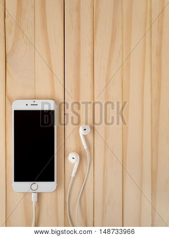 CHIANGRAI THAILAND -SEPTEMBER 15 2016: Front view image of new Apple iPhone7 mockup connecting with Lightning cable and Apple EarPods mockup on wooden background with copy space.