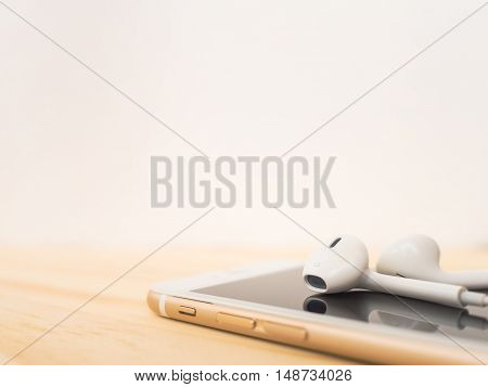 CHIANGRAI THAILAND -SEPTEMBER 15 2016: Close-up image of Apple EarPods on top of Apple iPhone 7 mockup and reflection on screen on wooden table with copy space.